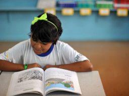 Imagem apresenta menina lendo material didático em sala de aula. Foto foi tirada por Marcello Casal, da Agência Brasil