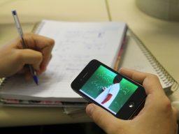 Estudante faz anotações em caderno enquanto assiste aula de matemática pelo celular