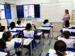 Alunos de escola municipal de Recife dentro de sala de aula, sentados e ouvindo professora.