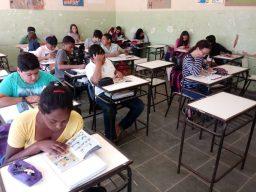 Escola rural de Espera Feliz (MG), antes da última reforma. 15 alunos em suas carteiras em sala de aula. as paredes estão descascando.